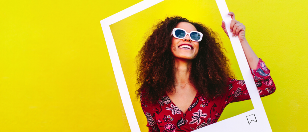 Woman holding social media frame yellow background - Rogers Advertising